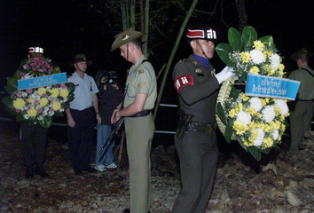 A THAI SOLDIER CARRIES A WREATH FOR NEW ZEALAND ON ANZAC DAY INTHAILAND.