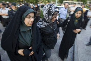 Iranian policewomen escort a woman to a police station in eastern Tehran