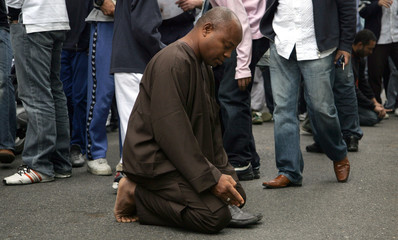 A man prays outside the entrance of the London Central Mosque during Friday prayers