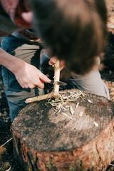 Tourist cutting branch to set up a campfire.