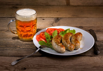 Glass of beer and sausages on the wood background
