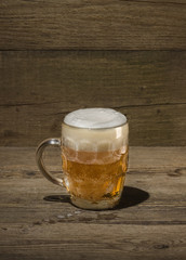 Glass of beer on the wood background
