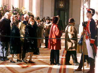Citizens queue next to a Spanish Royal soldier (R) as they wait to pay their respects for Spanish [K..