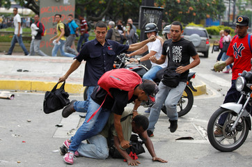 Opposition supporters hit a man they accuse of being a thief during a rally against President Nicolas Maduro in Caracas, Venezuela