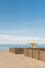 Beach with clear sky and yellow umbrella