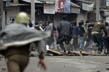 Indian policeman chases away Kashmiri protesters during protest in Srinagar