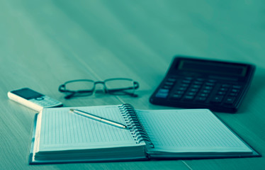 Notebook, calculatir, glasses and pen on the table