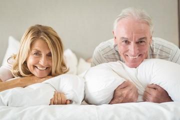 Portrait of happy senior couple lying on bed