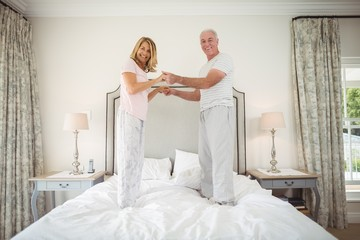 Portrait of happy senior couple dancing on bed