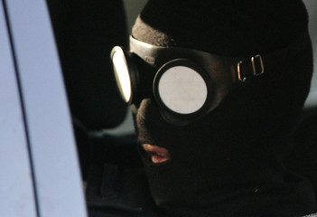 Masked suspect leaves courthouse in police cruiser in Brussels