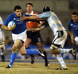 Italy's Masi tries to evade Argentina's Bouza during a rugby test match in Cordoba.