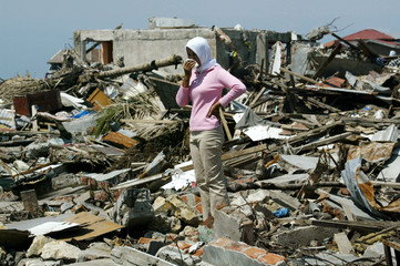 An Achenese woman stands alone amid debris in the tsunami-devastated city of Banda Aceh on the Indon..