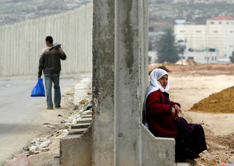 A Palestinian woman sits on part of Israeli security barrier in Ram.