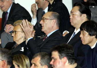 France's President Jacques Chirac (C) applauds as he attends the Spring Grand Sumo tournament in Osa..