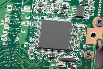 Electronic chip on a green circuit board close-up