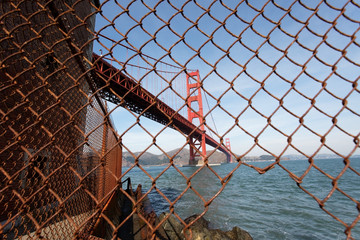 Unusual view of the Golden Gate Bridge seen through rusty chain link fence.