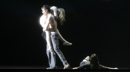 Actors Harzer as Raskolnikow, Burchard as Dunja and Schnoeink as Sonja perform on stage in Salzburg