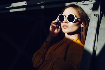 Indoor close up portrait of young beautiful fashionable woman wearing stylish white round sunglasses. Model posing on sunny and shadow sides. Female fashion concept. Copy, empty space for text