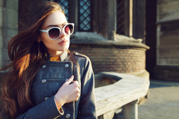 Outdoor close up portrait of young beautiful woman with long hair wearing stylish  blue sunglasses, jacket posing on street. Model looking aside. Female fashion concept. Copy, empty space for text