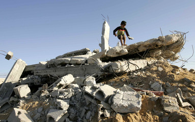 A Palestinian boy plays on top of a house owned by a Palestinian after local witnesses said was it demolished by an Israeli bulldozer in the southern Gaza Strip