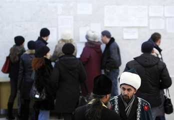 An Orthodox priest talks to his Muslim counterpart near people looking at lists of the victims of a fire in Perm