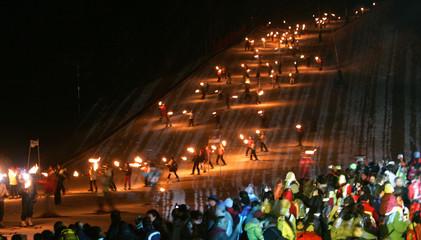 Around 2,000 skiers carrying torches ski down a hill to mark a new world record at La Masella ski resort near Barcelona