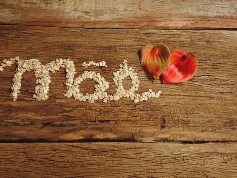 Grãos de aveia formando a palavra mãe com duas flores de antúrio ao lado sobre mesa de madeira rústica