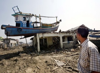 An Acehnese man looks at a boat left on top of a house as a result of the tsunami in Banda Aceh.