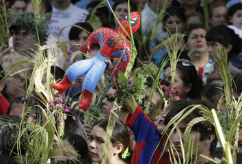 A man holds an inflatable Spiderman while Catholics participate in a procession celebrating Palm Sunday in San Lorenzo