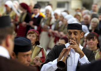 Macedonian plays trumpet while dressed in traditional folk costume during wedding ceremony in village of Galicnik