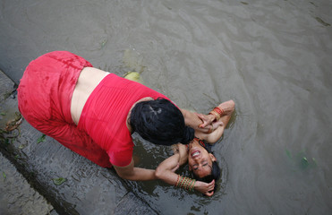 A Hindu woman celebrating the Rishi Panchami festival helps her friend to take a holy dip in the Bagmati River in Kathmandu