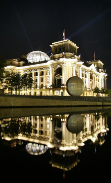Streams of light beam from cupola of the Reichstags building as the facade is illuminated by energy saving lamps in Berlin