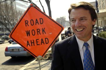Former U.S. Senator John Edwards and presidential hopeful walks past a road construction sign while traveling between campaign appearances in Washington