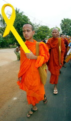 A Cambodian buddhist monk (L) holds a yellow symbol for freedom of expression as he walks with other..