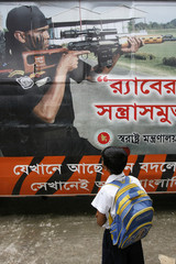 A school boy looks at a picture of the Rapid Action Battelian on a bus before the closing ceremony of its road show in Dhaka