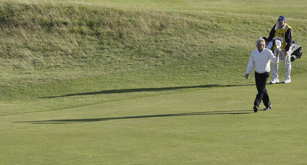 Greg Norman of Australia and his caddie Linn Strickler walk up the 18th fairway at the 2008 British Open Golf Championship at Royal Birkdale