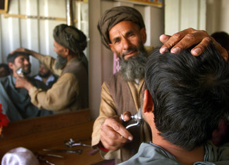 A young Afghan has a shave for the first time after 5 years of Taliban Sharia law in a barber shop i..
