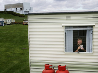 Woman sits at the window of her caravan holiday home, with Torness nuclear power station in the background, in East Lothian