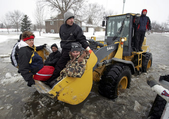 Volunteers ride in tractor after sandbagging around home threatened by flood waters from Red River in Fargo