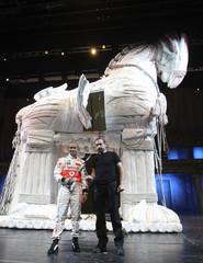 McLaren's Formula One driver Hamilton of Britain holds the swords with the art director Mustafa Erdogan of the Troy (Troya), portraying the legendary Trojan War as they pose under the Trojan Horse on stage in Istanbul