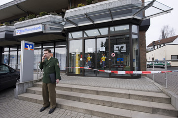 A German police officer makes a phone call outside a regional bank in the small town of Ruppichteroth some 50 km west of the German city of Cologne