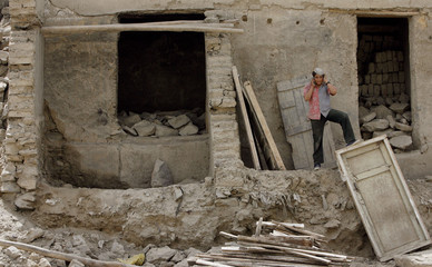 A boy speaks on a mobile phone as he stands in front of a ruined house in Kabul