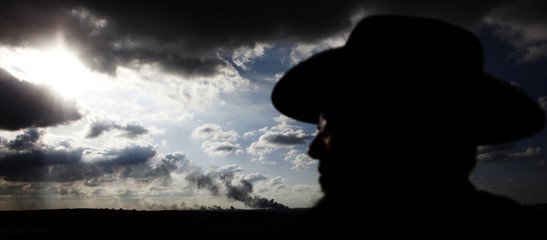 An ultra-Orthodox Jewish man watches Israel's offensive from a hill just outside the northern Gaza Strip