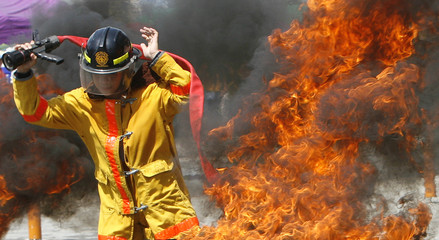 A fireman holds a water hose as he prepares to extinguish a fire during the Fire Volunteer Olympics in Manila