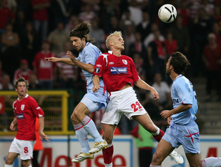 Standard Liege's Karel Geraerts jumps for a header with Celta Vigo's Diego Rodolfo Placente and Matias Emanuel Lequi during their UEFA Cup first round soccer match in Liege