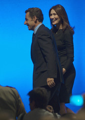 France's President Nicolas Sarkozy holds his wife Carla Bruni Sarkozy's hand as they arrive at a meeting with the French community in New York