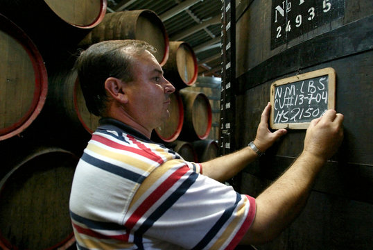 -PHOTO TAKEN 13OCT04- A worker writes information on the slate sign of a huge cask of Madeira wine i..