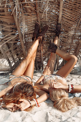 two attractive young woman lying down on sand on beach
