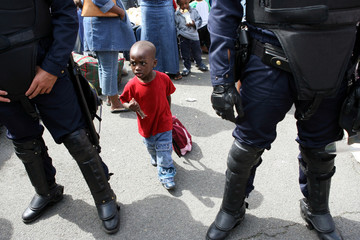 Child walks in between riot policemen after police evacuated about 1, 000 people from France's biggest squat near Paris