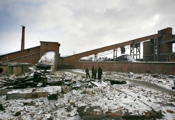 Chinese men stand at site of coal mine blast in Qitaihe